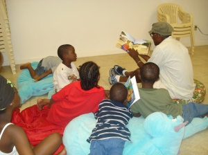 In this photo from the Cushion Club archives, Cedric reads to some of the children.