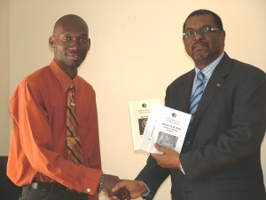 Craig presenting copies of the three collections from the programme to National Security Minister Dr. Errol Cort.