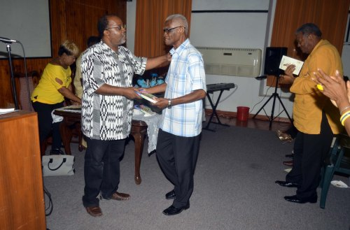 Marcus Christopher accepting a copy of Nobody Go Run Me from Dorbrene O'Marde (Photo courtesy Colin Cumberbatch)