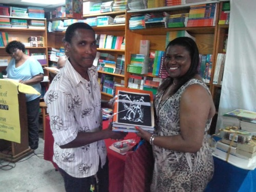 Wadadli Pen 2014 visual artist winner Alvin Livingstone is also a teacher and a musician. That's an image by another artist Edison Liburd he's holding. And that's writer D. Gisele Isaac presenting his prize package at the 2014 awards ceremony.
