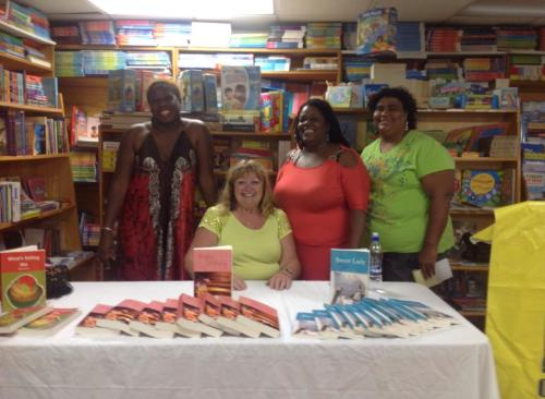Elaine seated, with copies of Singles Holiday, its sequel Sweet Lady, and first book What's Eating Me? laid out before her and from left, me, Marcella Andre and Barbara Arrindell standing alongside.