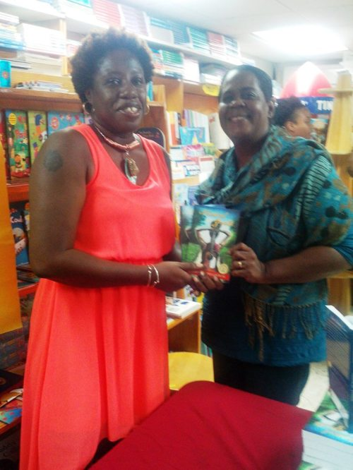 CODE, publisher Caribbean Reads, and me contributed copies of Musical Youth to the Public Library; here I am presenting those copies to the library representative.