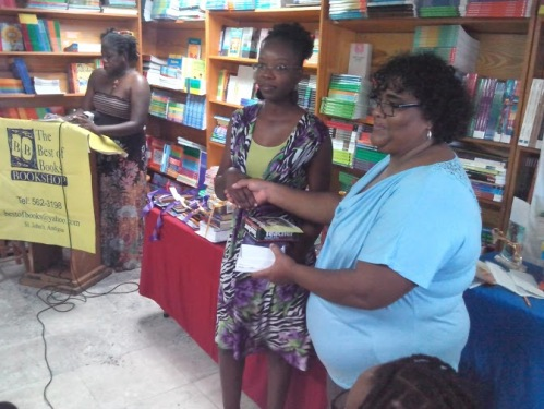 Best of Books, a patron of the Wadadli Youth Pen Prize from the beginning has hosted the awards ceremony since 2011. Pictured is store manager Barbara Arrindell making a presentation to educator Paula Russell Peters who was a 2014 finalist for the WP 10th anniversary Teachers Prize and who also collected on behalf of T N Kirnon which netted a prize for the most submissions from a single school. In the background is WP founder and coordinator, author Joanne C. Hillhouse.