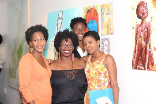 "A ""911"" representative, left, with Zahra Airall of theatrical advocacy group Women of Antigua, centre, and new DOGA director Famarla Jacobs, right with artist Martiza Martin and some of the art work on display behind them."