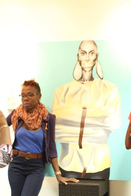 Claytine Nisbett, a former Wadadli Pen volunteer, and founder of Walking in to Walls (an online advocacy project), alongside art work by X-Sapphair King.