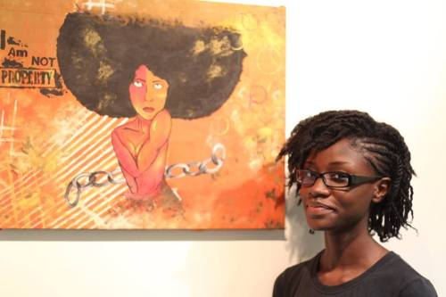 Artist Kimberley Gordon posing with her art work.