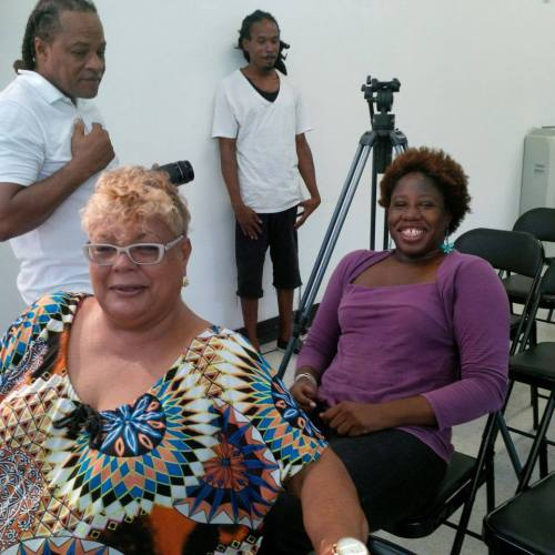 Me (in purple) and Jennifer Hector, widow of the late Leonard Tim Hector. In the background, media covering the event.